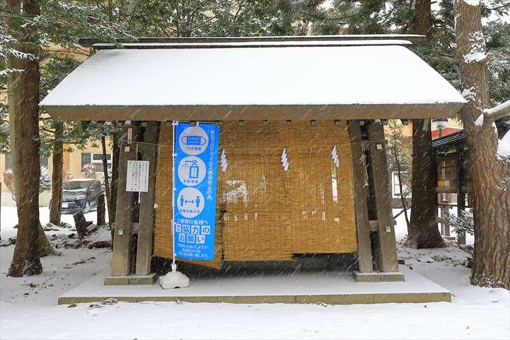 雪降る琴似神社の手水舎